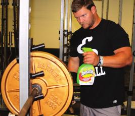 Austin Feddersen sprays down disks in the weight room