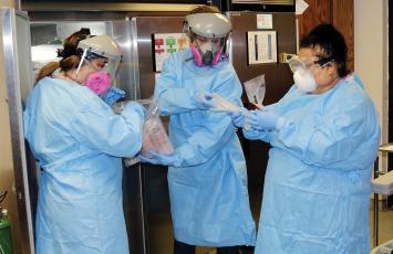 Canadian County Health Department workers wear full personal protection equipment