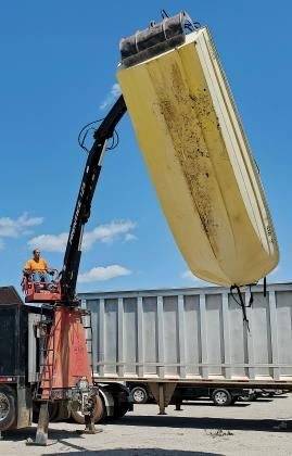 A worker uses a crane to lift a boat into a dumpster