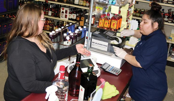Martinez of Route 66 Liquor waits on Combs