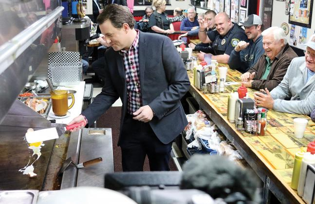 Todd Piro cracks an egg during a live shot at Sid's Diner
