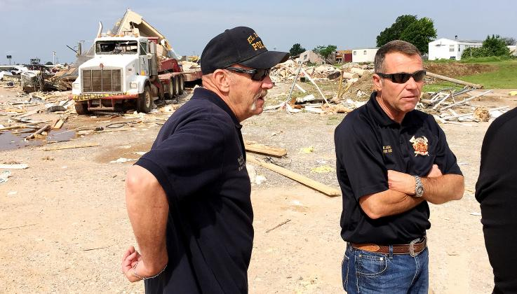 Ken Brown, left, and Kent Lagaly discuss tornado damage