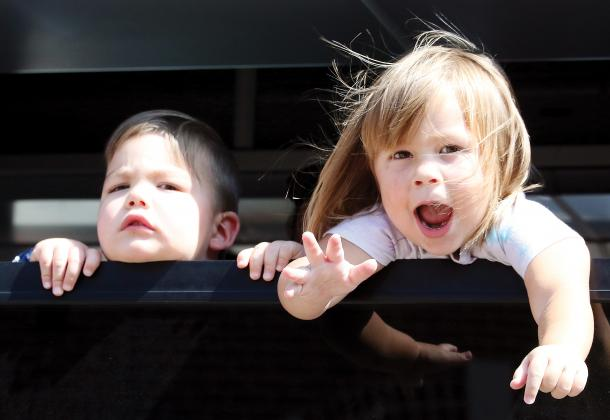 Two children look at the crowd out a bus window