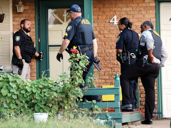 El Reno police, with guns drawn, prepare to execute a search warrant