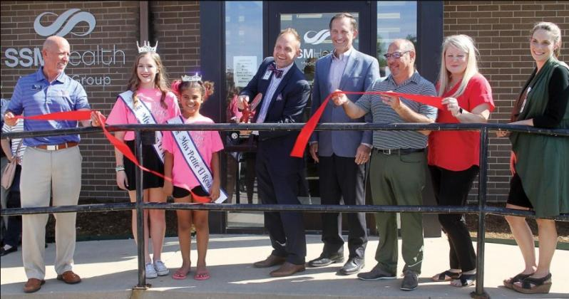 Members of the El Reno Chamber of Commerce gather as Dr. Kevin Lewis cuts the ceremonial ribbon outside the SSM Saint Anthony's Clinic.