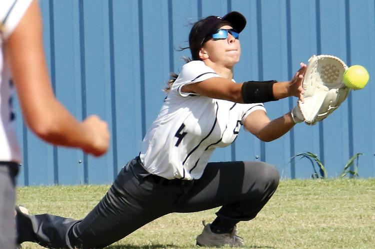 Krystiana Guzman slides down to her knees to try and scoop up a hit
