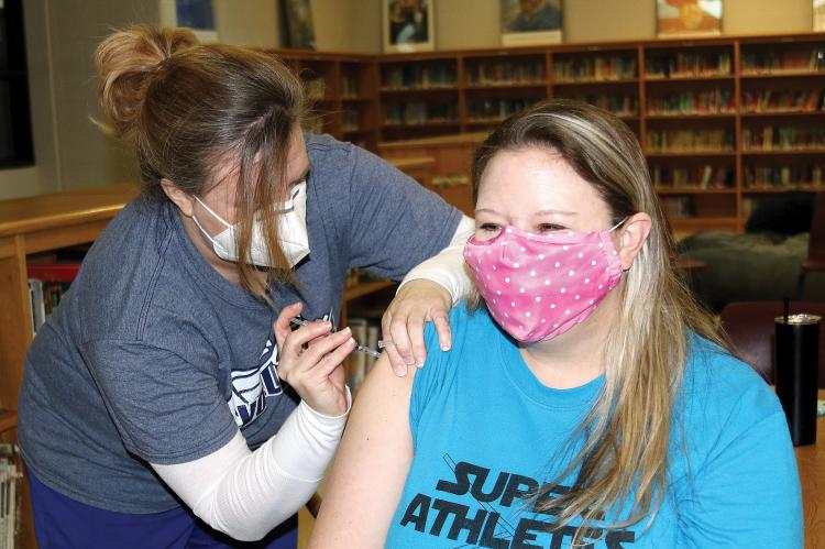 Katie Scheirer squints as Nicki Cerne sticks a needle into her arm