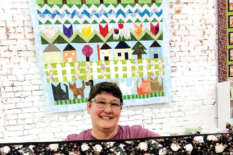 MaCrae Putnam shows off some of the quilts to be displayed
