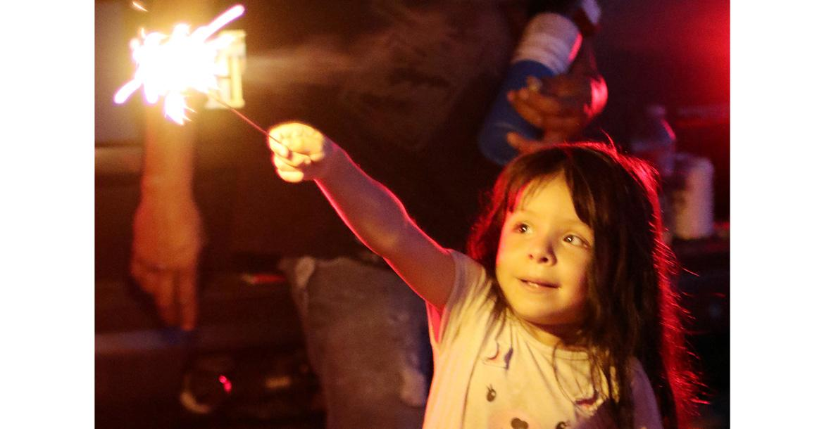 Isabelle Arias stares at a sparkler_slideshow