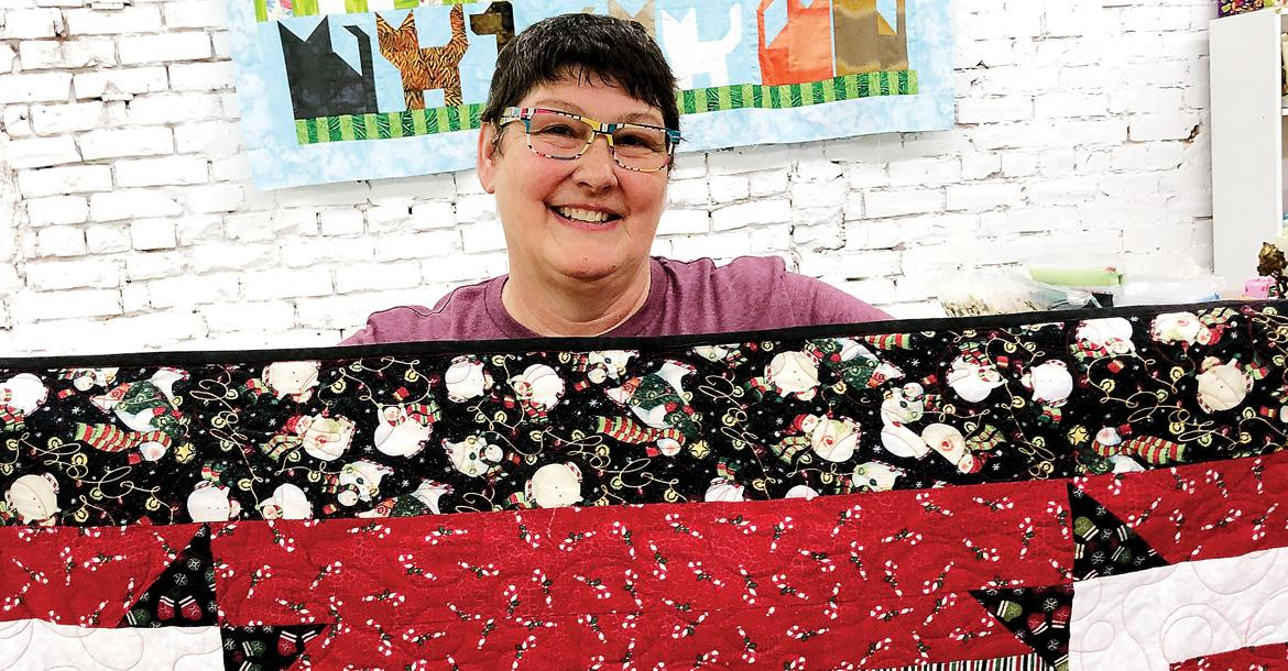 MaCrae Putnam shows off some of the quilts to be displayed_slideshow